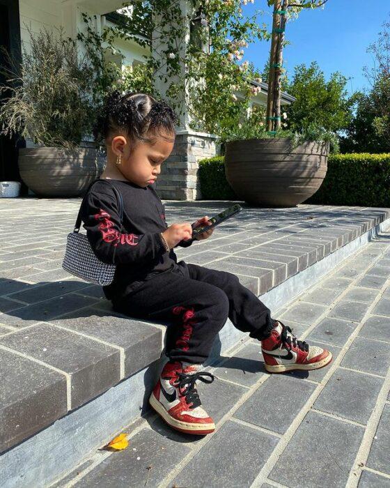 Stormi viendo su telefono mientras está sentada en las escaleras de su casa