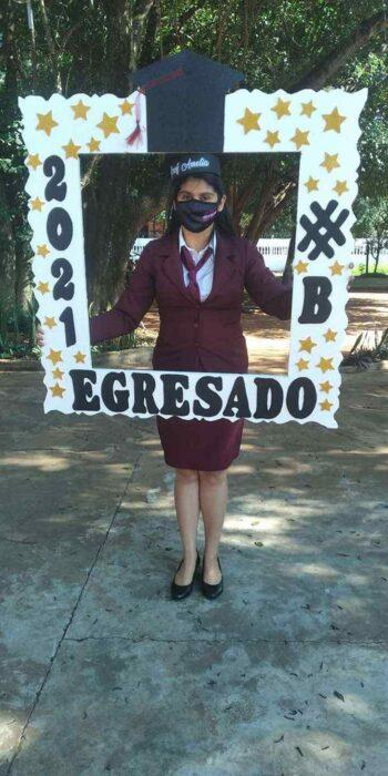 Mujer sosteniendo un marco de graduación ;Mamá soltera se titula como profesora luego de vender pan y sopa en las calles