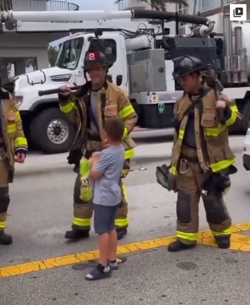 Niño repartiendo dulces a los bomberos en el derrumbe de Miami