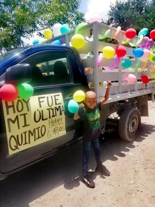 Niño posando junto a una camioneta llena de globos