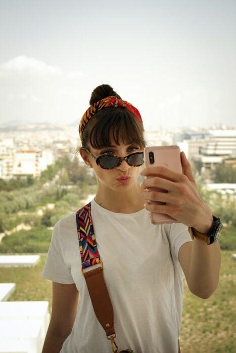 Chica tomando selfie ;Nueva ley determina que las influencers deberán declarar si retocaron sus fotos o no