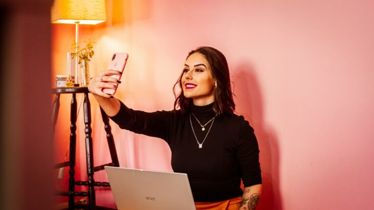 Chica tomando selfie frente a una computadora ;Nueva ley determina que las influencers deberán declarar si retocaron sus fotos o no