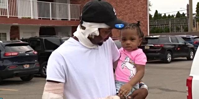 hombre cargando a su bebé en brazos; Papá arriesga su vida en un incendio para salvar a sus gemelas
