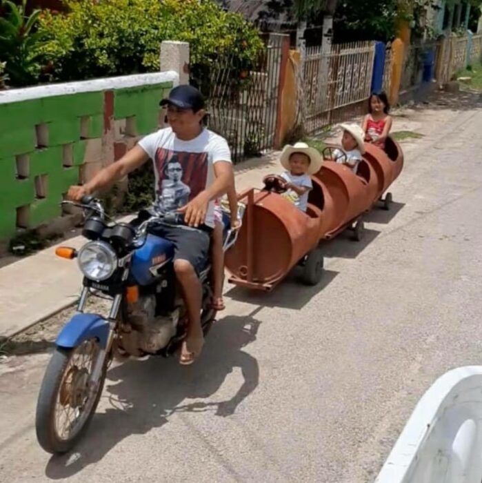 Padre e hijos paseando en un tren de metal ;Papá crea trenecito con botes de metal para sus hijos