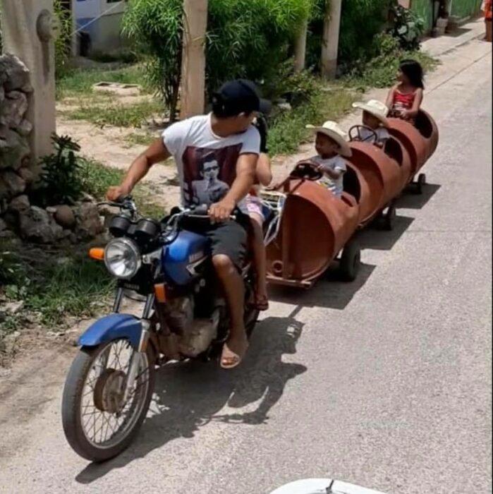 padre e hijos de paseo; Papá crea trenecito con botes de metal para sus hijos