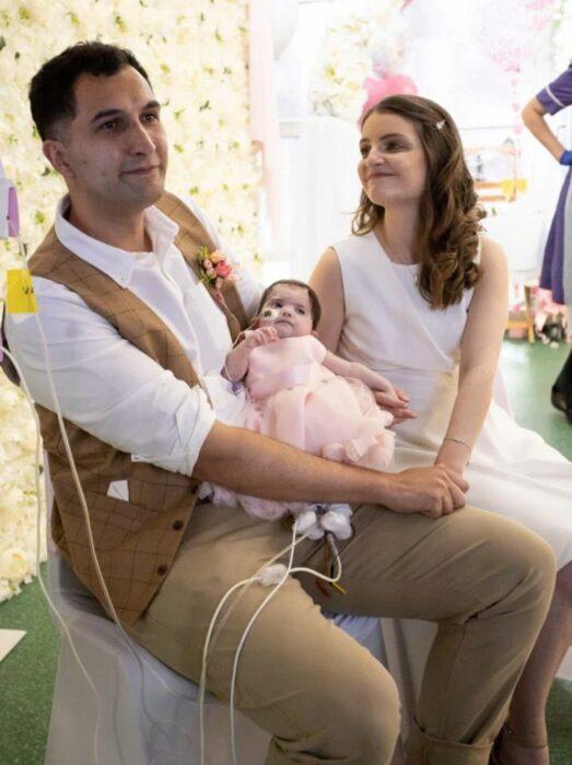 Pareja sosteniendo a su bebé el día de su boda