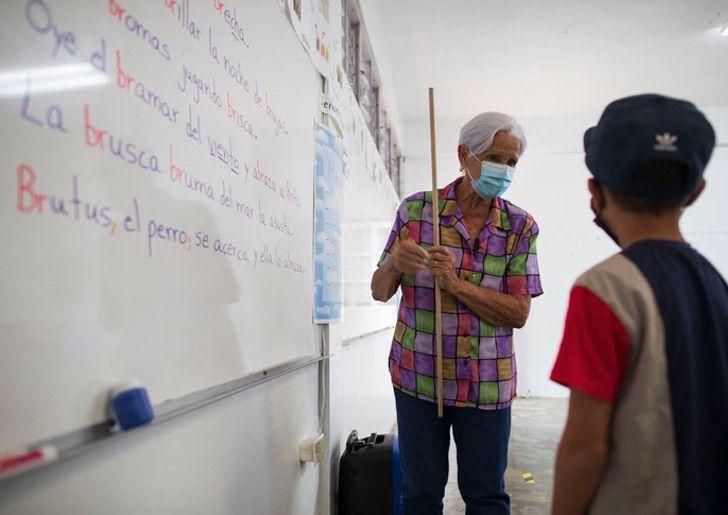 Lilia María Rivera Morales, profesora, enseñando a alumno ;Profesora de 89 años sigue educando a los niños de Puerto Rico (1)