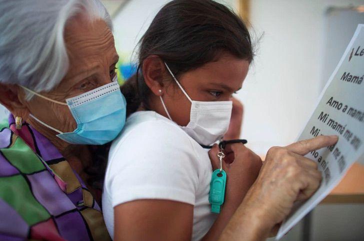 Lilia María Rivera Morales, profesora ayudando a alumna con sus estudios; Profesora de 89 años sigue educando a los niños de Puerto Rico