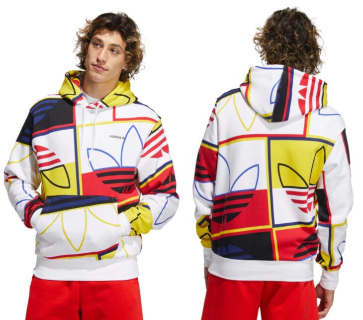 Chico modelando una sudadera de adidas Forum, color blanco con colores amarillo y rojo