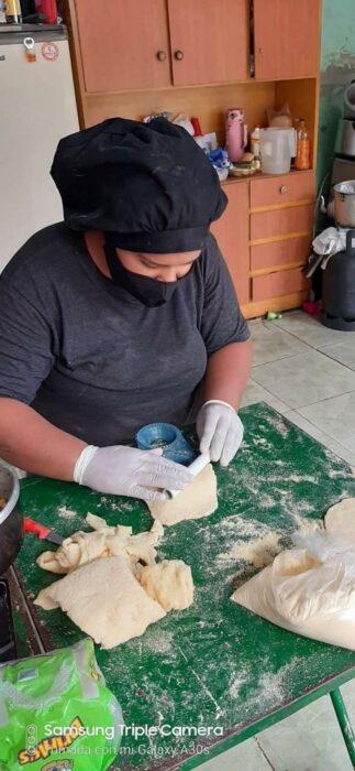 Chica cocinando empanadas ;Vende empanadas caseras para cumplir su sueño de ser militar e internet ya salió al rescate