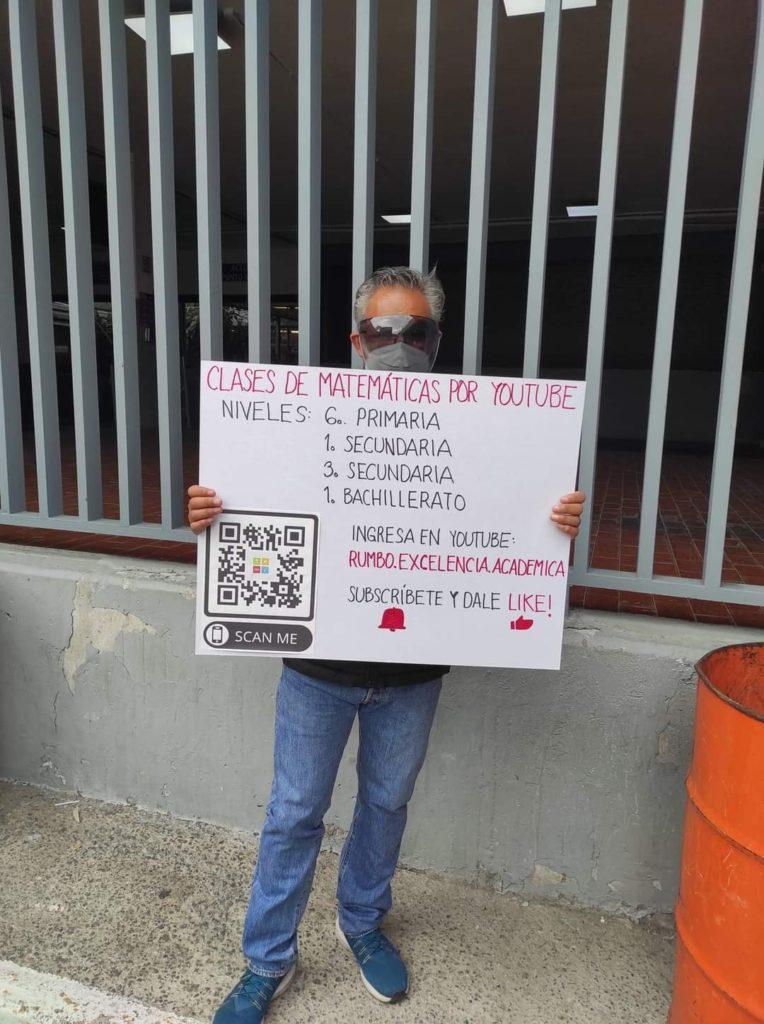 Hombre sosteniendo un letrero; ¡Con letrero en mano! Maestro de matemáticas promociona sus clases en YouTube