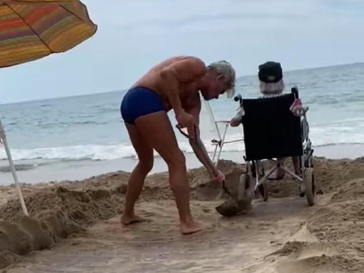 Hijo abre camino en la arena para que su mamá en silla de ruedas llegue a la orilla del mar