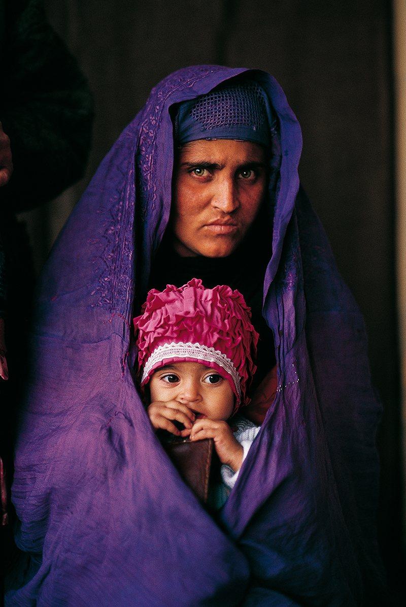 Mujer cargando a una niña; La niña de National Geographic que refleja los cambios en Afganistán. Una vida bajo las sombras