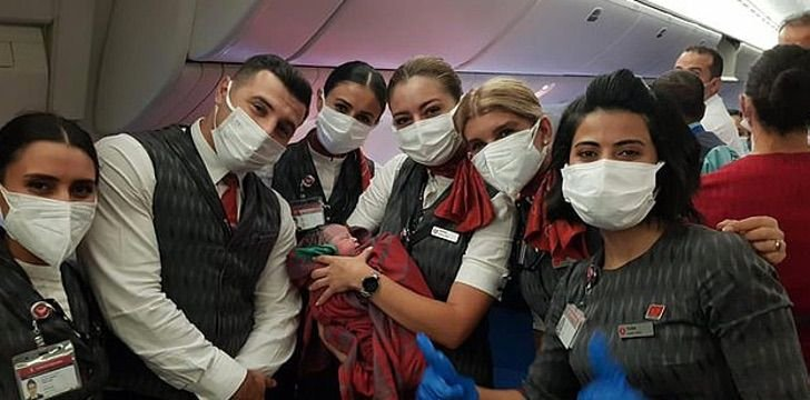 Asistentes de vuelo sosteniendo a una bebé que nació durante un viaje