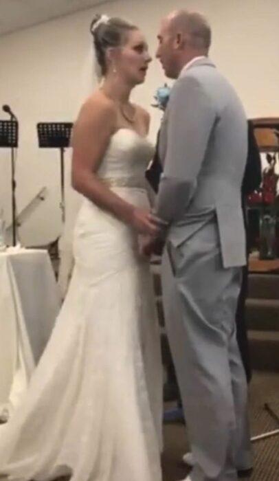 pareja de novios viéndose fijamente mientras están en su boda