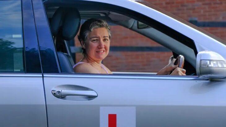 Mujer conduciendo un automóvil de color gris