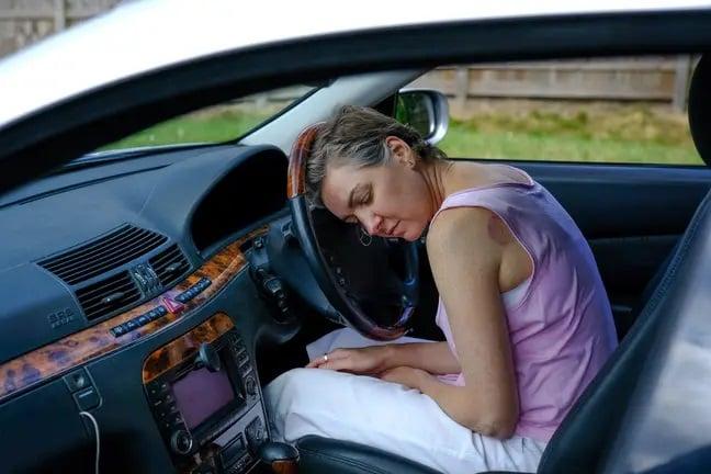 Mujer durmiendo en un coche mientras está estacionada