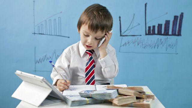 Niño haciendo negocios mientras está sentado en un escritorio