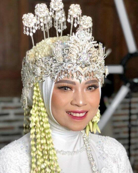 Novia usando un maquillaje y corona el día de su boda