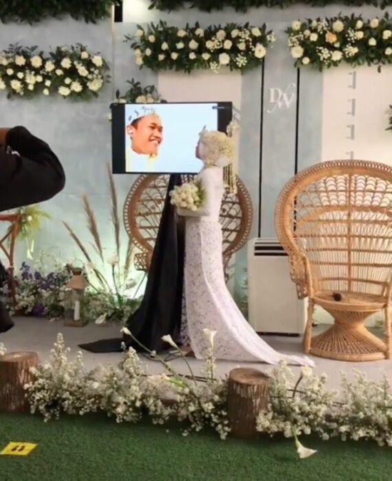 Novios el día de su boda casándose a través de una pantalla