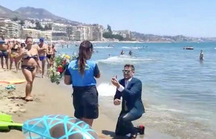 Hombre con la rodilla en la playa proponiendo matrimonio