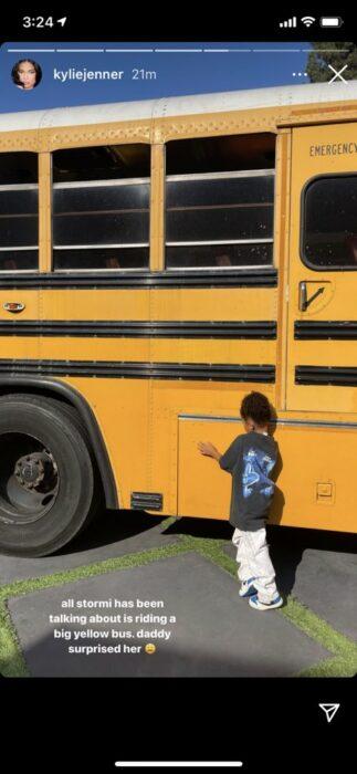Stormi tocando un autobús amarillo
