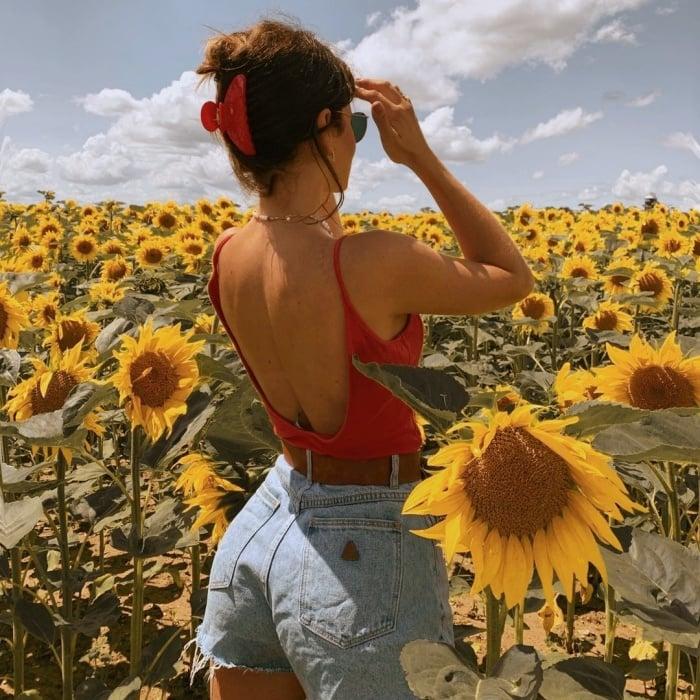 chica posando de manera original, con flores, en un campo abierto, frente a un espejo, con ropa trendy, jeans, falda, outfit lindo, botas, manicure, uñas postizas, lentes de sol