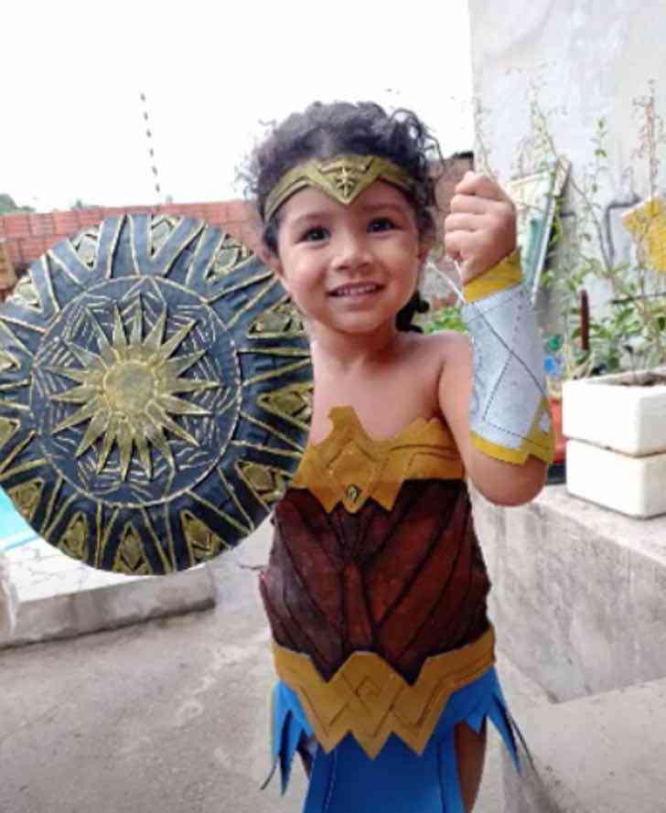 Niña sosteniendo un escudo de la Mujer Maravilla; Abuela creó un bello disfraz de Mujer Maravilla para su nieta
