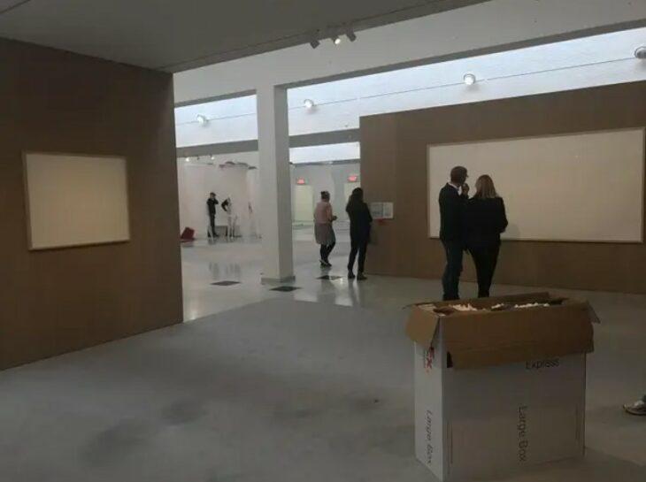 Artista mostrando su obra de dos lienzos vacíos