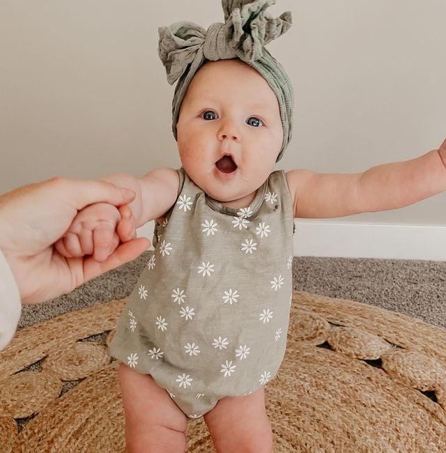 Bebé de cuatro meses sonriendo mientras está sentada