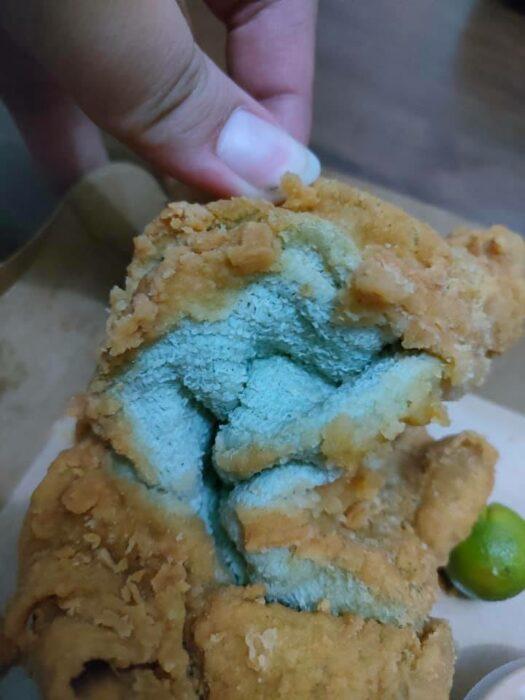 Chica abriendo un pollo frito que en realidad era una toalla