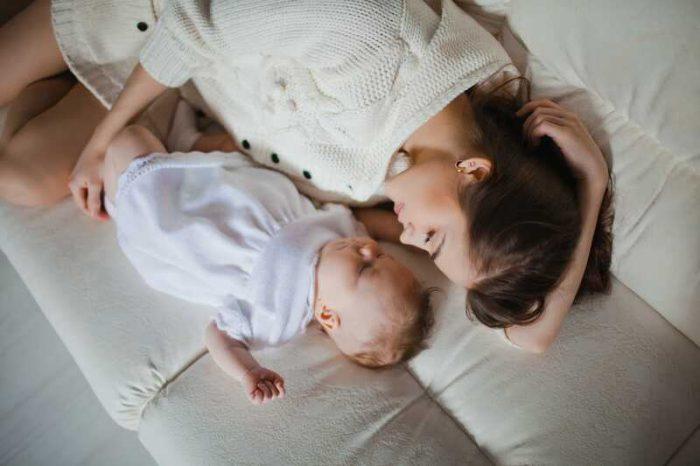 Mujer durmiendo con su bebé; Francia presentó una ley para proteger a las mujeres que amamantan en público