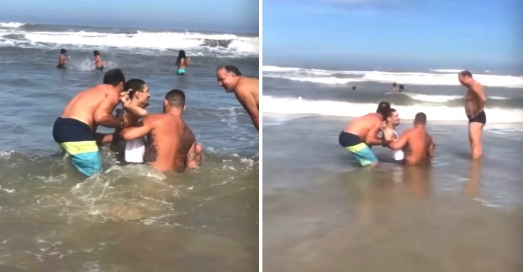 Hombres dentro del mar; Hombres ayudaron a un papá para que su hijo con discapacidad se bañara en el mar