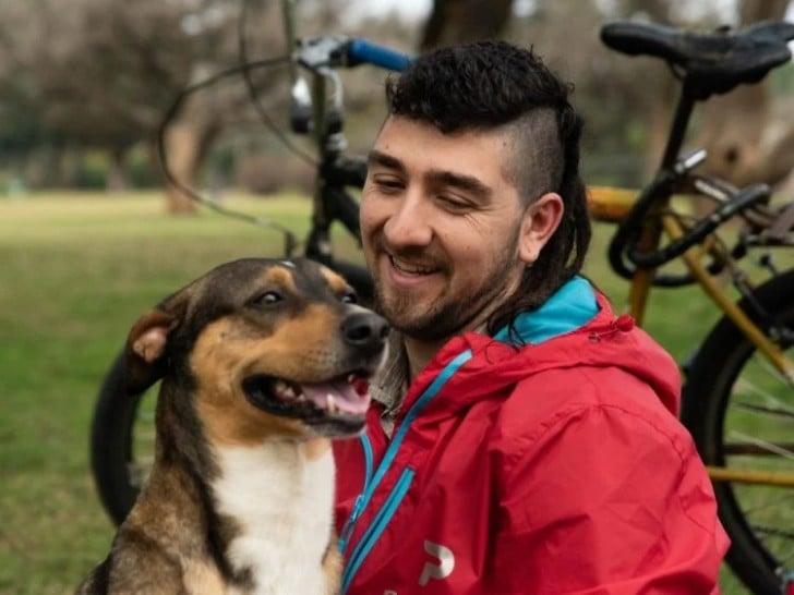 Joven y su perrito posando juntos en una bicicleta