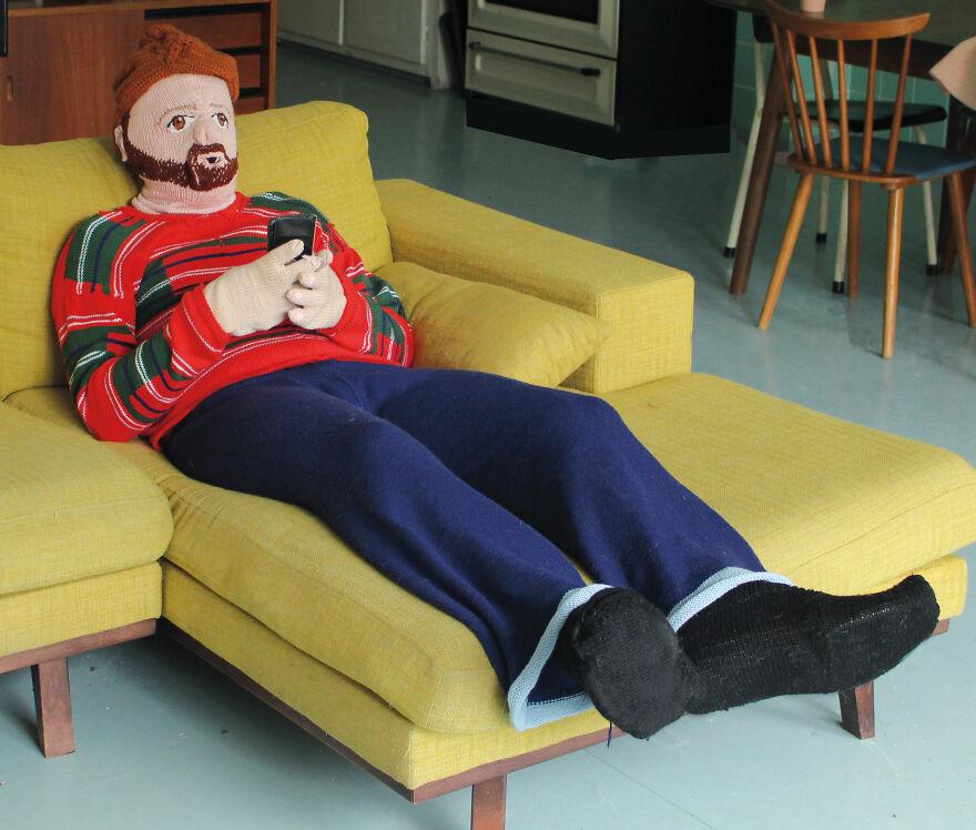 Muñeco tejido, recostado en un sofá; Mujer teje a su esposo e hijo en tamaño real