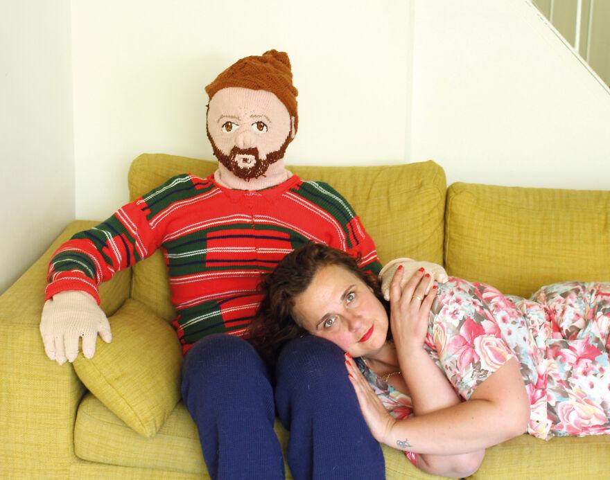 Mujer recostada sobre un muñeco tejido; Mujer teje a su esposo e hijo en tamaño real