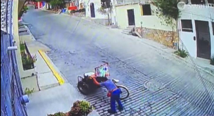 Hombre subiendo una colina empinada mientras sujeta su triciclo