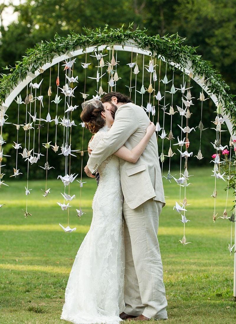 novios en altar con pájaros de papel ;15 Altares de boda que te harán decir: 'Sí, acepto'