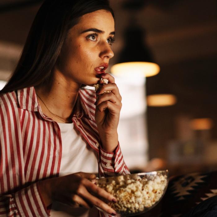 chica viendo películas de terror comiendo palomitas