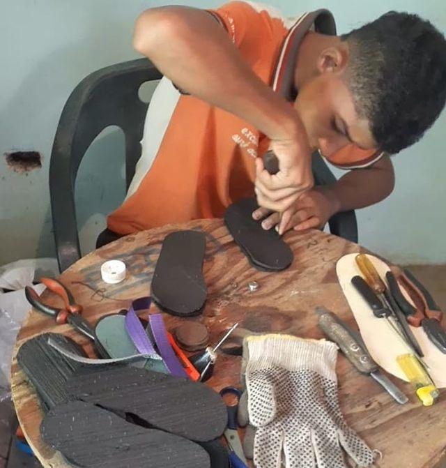 Chico haciendo chancletas con llanta