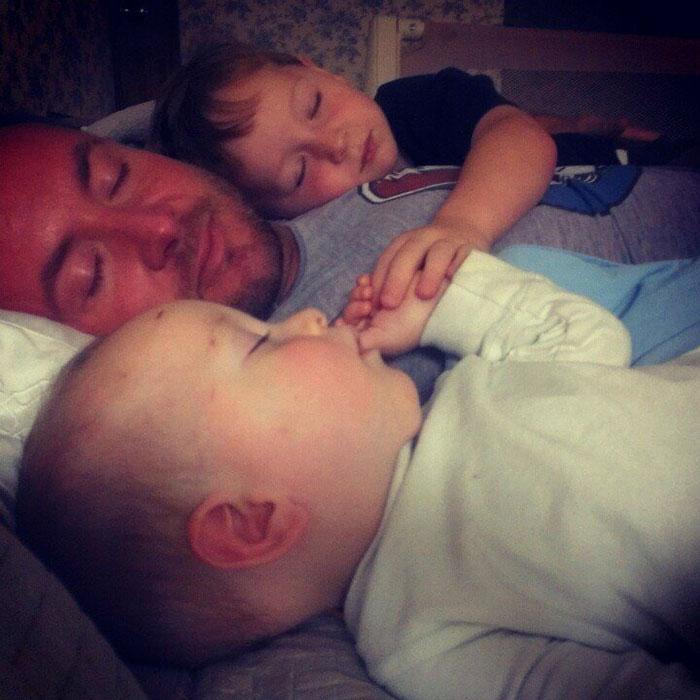 Papá recostado junto a sus hijos durmiendo