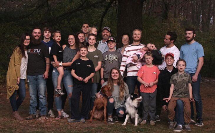 Familia de 14 integrantes posando para una fotografía en medio del bosque
